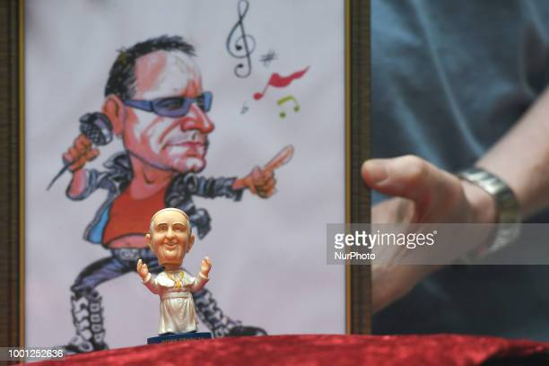 A mini size Pope Francis Bobble head in front of a watercolor caricature which features the Irish singersongwriter Bono made by an Irish Artist Ray...