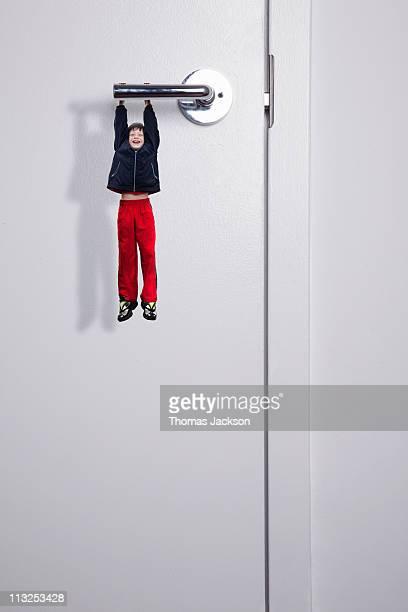 Miniature boy hanging from door handle