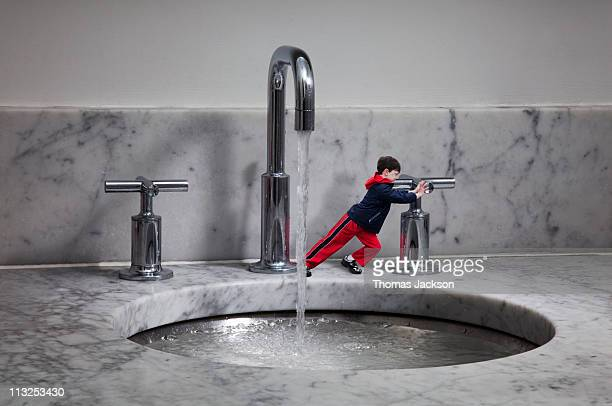 miniature boy turning off water tap - turning on or off stock pictures, royalty-free photos & images