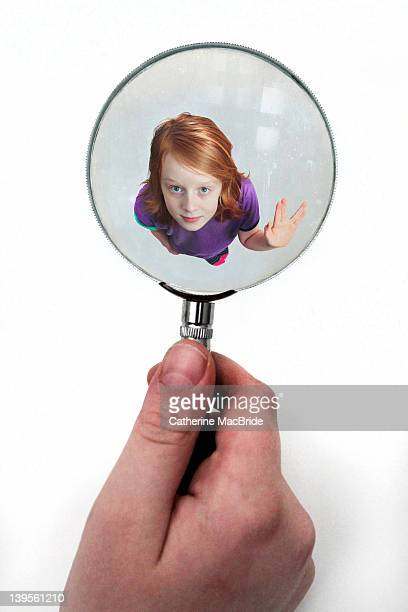 Miniature boy viewed through magnifying glass