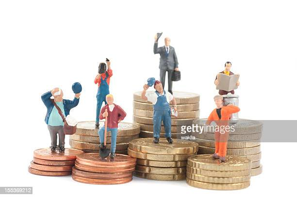miniature business people on stacks of coins - employment law stock photos and pictures