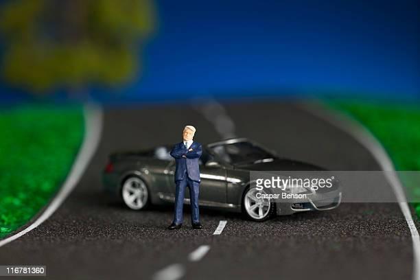 A miniature businessman figurine and miniature sports car