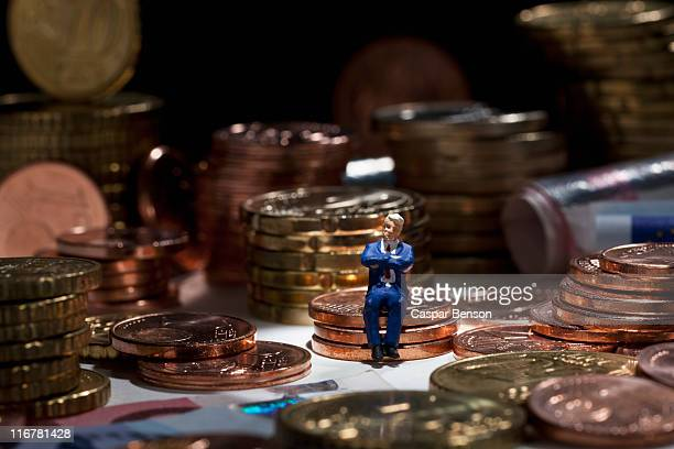A miniature businessman figurine with arms crossed sitting on a stack of coins