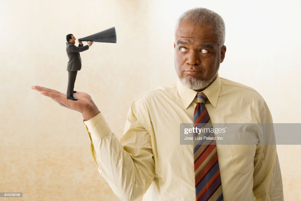 Miniature businessman speaking with bull horn to giant businessman : Stock Photo