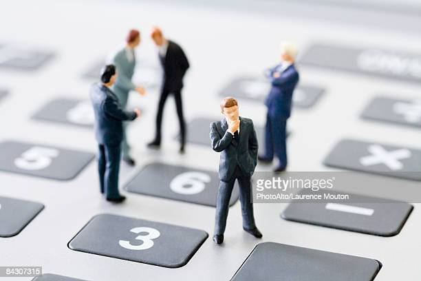 miniature businessmen standing on calculator - 人の姿 ストックフォトと画像