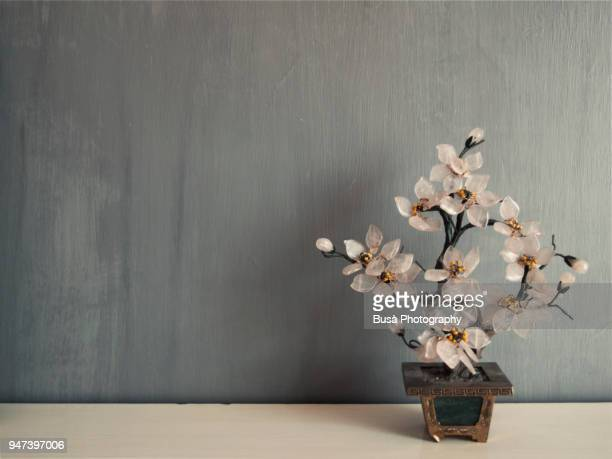 Miniature cherry tree made of glass against a grey background