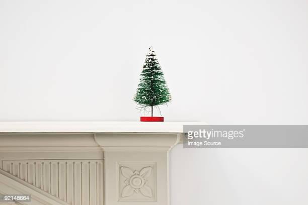 Miniature christmas tree on mantlepiece
