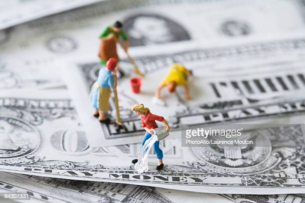 miniature cleaning ladies washing play money - money laundering stock photos and pictures