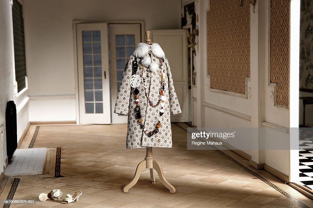Miniature coat on tailor's dummy in doll house living room : Foto de stock