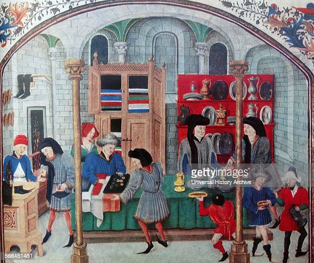 Miniature depicting urban Mediaeval life. Inside a covered market there are a number of stalls selling items including a shoemaker, a cloth merchant...