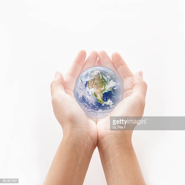 a miniature earth is on the palms.  - world at your fingertips stock pictures, royalty-free photos & images