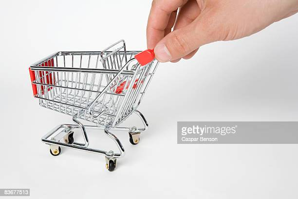 A miniature empty shopping cart being pushed by human fingers