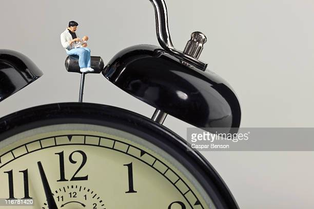 A miniature father figurine holding his baby while sitting on an alarm clock