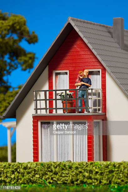 A miniature father figurine holding his daughter on the balcony of a dollhouse