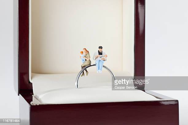 Miniature figurines of a young family sitting on a wedding ring in a jewelry box