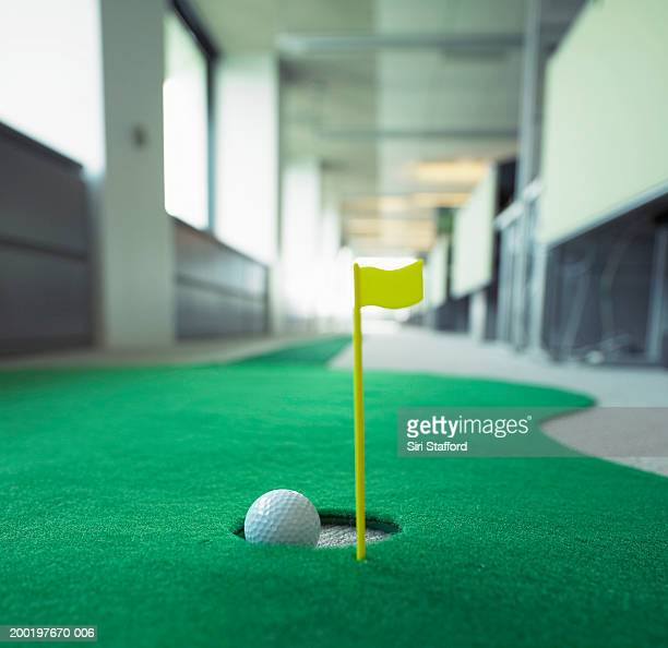 Miniature golf in office, focus on hole