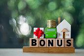 Miniature home, car and money put on wood block in word BONUS. Yearly bonus concept. Bonus is motivation in work