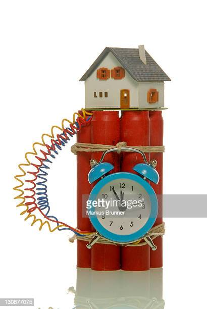 Miniature house on a bomb, symbolic image of a hazardous housing market
