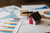 Miniature House on A Financial Graph