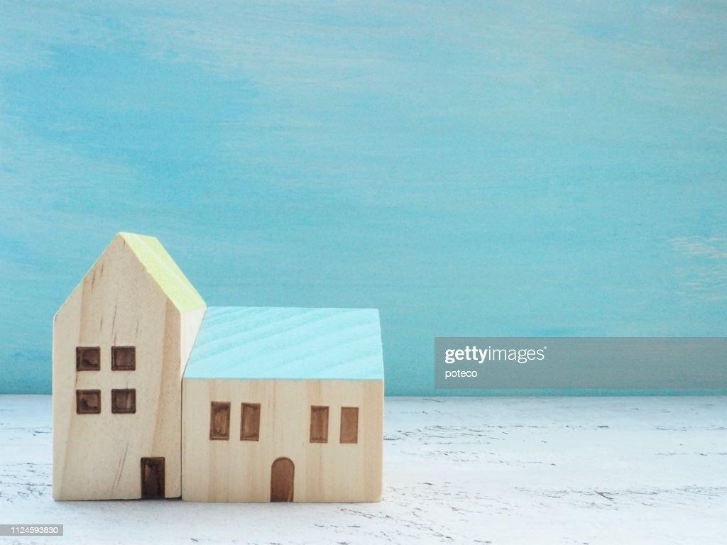 木製の青空と青い背景を持つミニチュア家立っています。 : ストックフォト