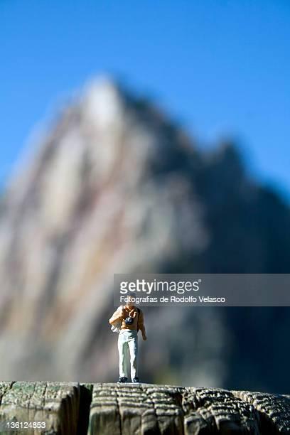 Miniature human figure walking on mountain