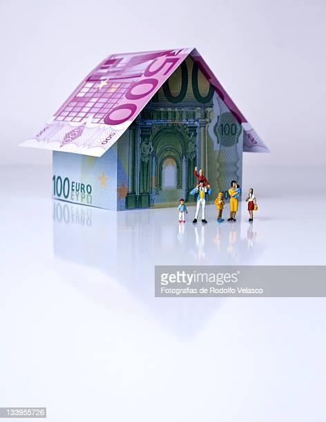 miniature human figures in front of his house - billete de banco de quinientos euros fotografías e imágenes de stock