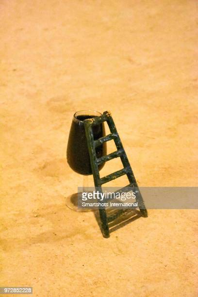miniature ladder inviting small rodents and other sympathetic creatures to climb up for a sip of red wine inside a cellar in sherry country in andalusia, spain - ヘレスデラフロンテラ ストックフォトと画像