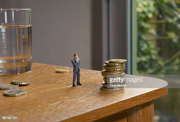 miniature man looking at pile of coins on table - figurine stock pictures, royalty-free photos & images