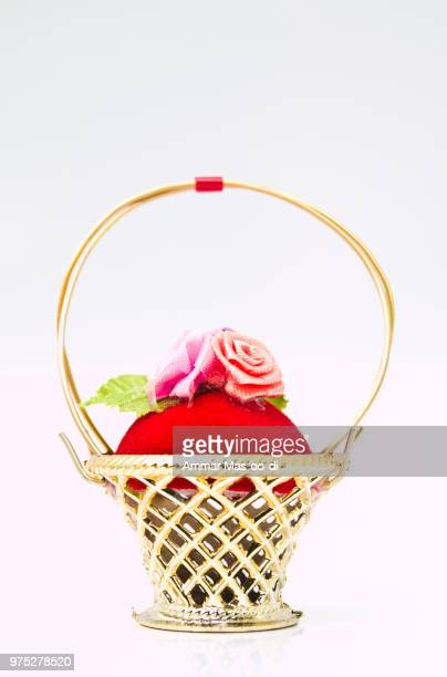 a miniature metalic wicker decorated by roses on a red velvet is - animal internal organ stock photos and pictures