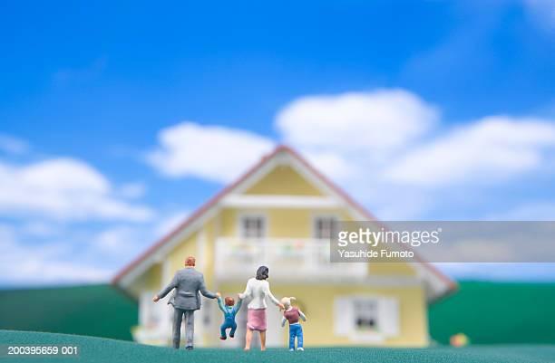 Miniature model family walking toward house, rear view