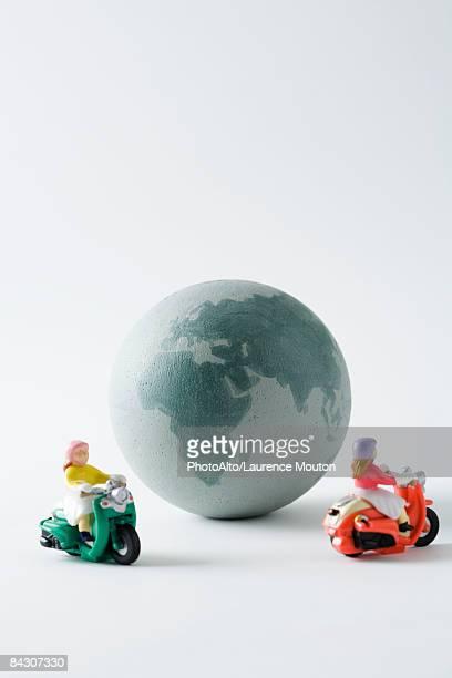 Miniature mopeds circling globe