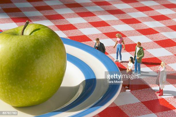 miniature people looking at apple