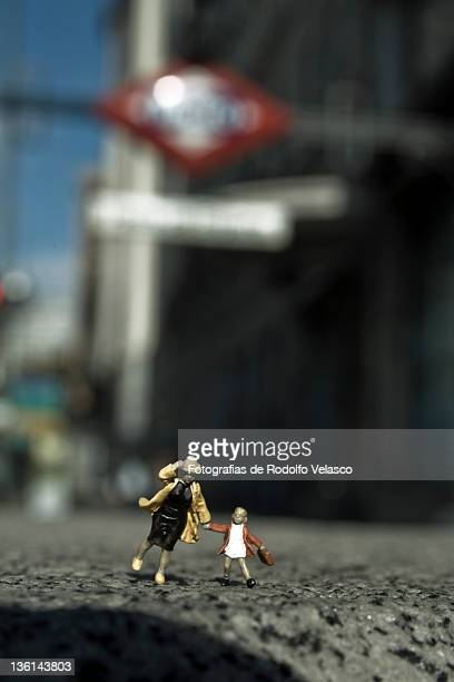 Miniature people running through streets