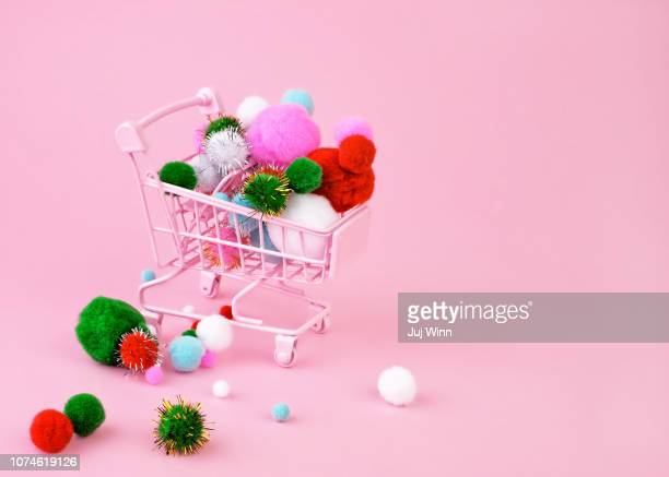 Miniature pink shopping cart overflowing with festive pompoms on a pink background.