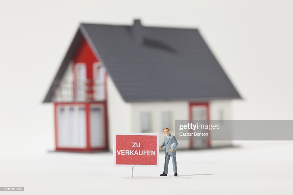 A miniature real estate agent figurine next to a ZU VERKAUFEN (for sale in German) sign : Stock Photo