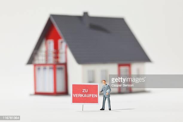 A miniature real estate agent figurine next to a ZU VERKAUFEN (for sale in German) sign