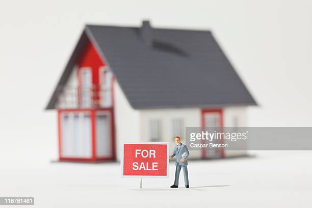A miniature real estate agent figurine standing next to a FOR SALE sign