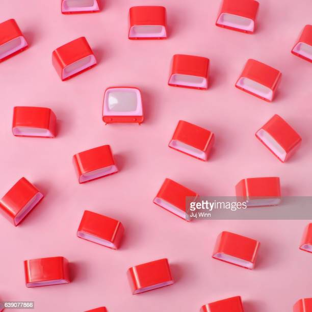 Miniature red toy televisions on pink background