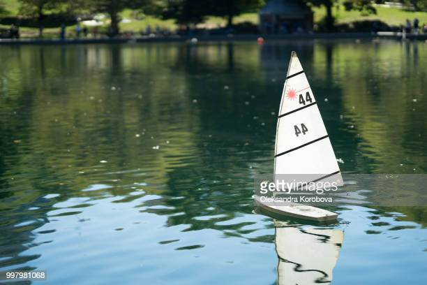 Miniature remote-controlled sail boat on the surface of a pond during a sunny day.
