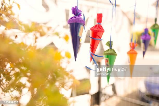 miniature school cones hanging in a row - der erste schultag stock-fotos und bilder