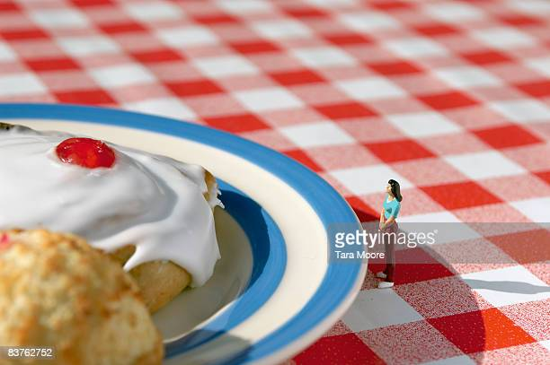 miniature woman looking at cakes