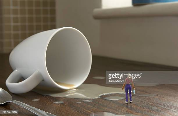 miniature woman standing by cup that has fallen