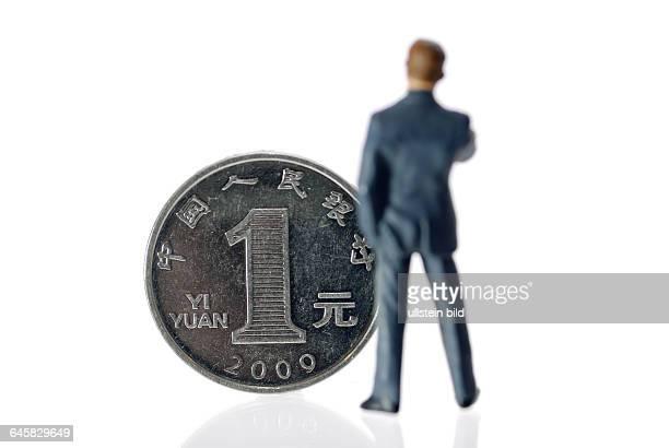Miniaturfigur eines Geschäftsmannes vor einer EinYuanMünze