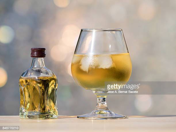 minibar bottle and glass of whiskey with ice on a wooden table illuminated by sunlight - liqueur stock pictures, royalty-free photos & images