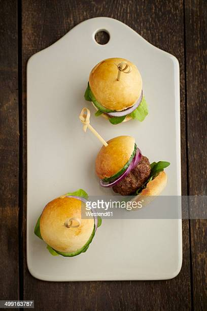 Mini-Burger with mincemeat, salad and red onions on white chopping board