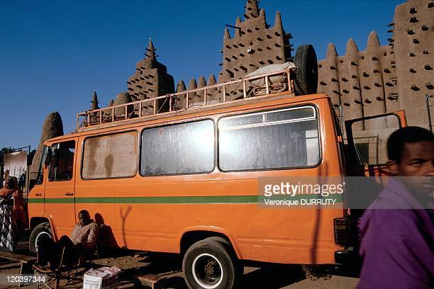Minibus front of the grand mosque of Djenne in Mali Asleep all week the city of Djenne wake up every Monday market day That day many transits liaise...