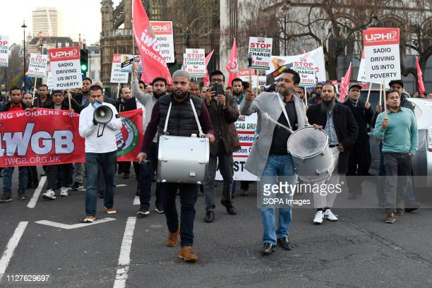 Minicab drivers seen playing drums during the protest Minicab drivers blocked Parliament Square in protest over changes to the congestion charge...