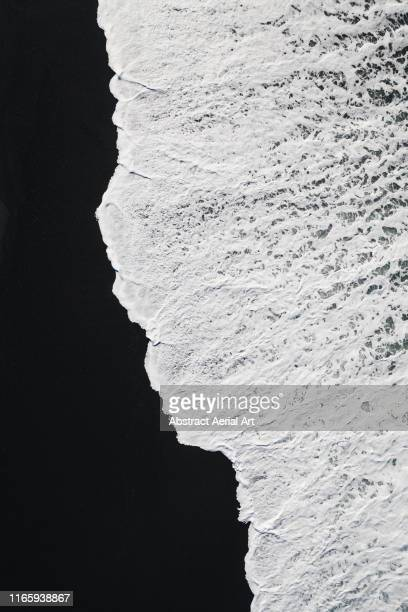 minimal aerial shot of wave washing onto volcanic black sand beach, lanzarote - black and white nature stock pictures, royalty-free photos & images