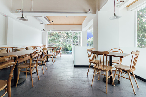 Minimal bread cafe decorating with white wall and wooden chairs. Warm, cozy and comfortable. 1063776368