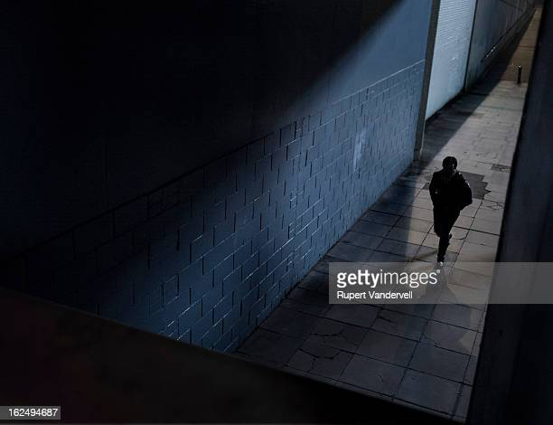 Minimal colour night image of a dark, silhouetted figure walking towards a tunnel with a descending shadow line. The image contains geometrical...